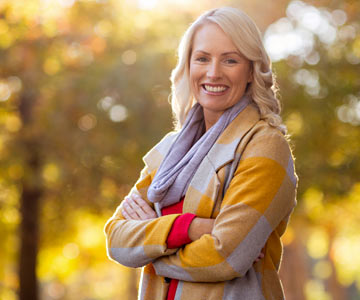 Middle-age woman smiling outdoors in the autumn.